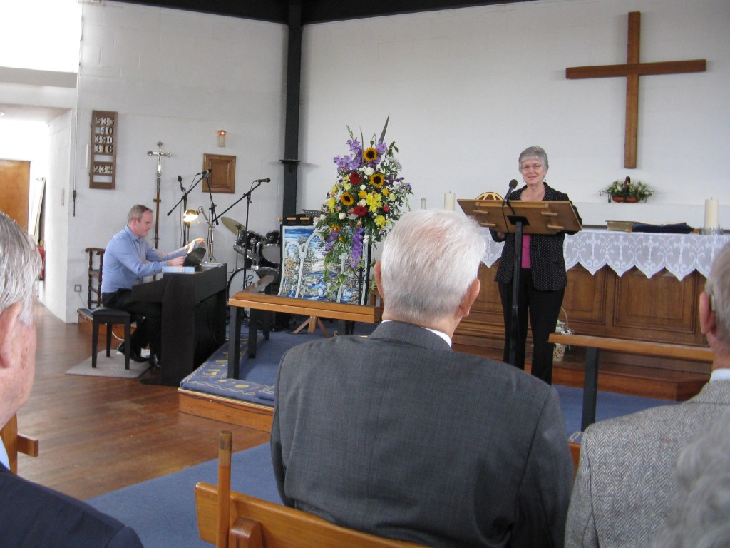 Shirley Henderson leads hymns while David Brace plays piano
