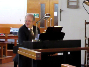 Mike Hustwait playing piano for hymns in Watford 2015-06-13
